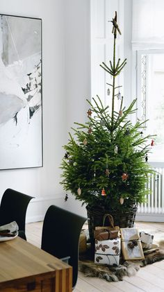 hjørnet af spisestuen står et rødgrantræ, der holder den klassiske og rolige stil, pyntet med glaspynt fra Brink. Hanne Berzant synes, at vi i en del år har set skæve og afpillede juletræer, og hun synes, at det er på tide at vende tilbage til de helt klassiske træer uden så mange dikkedarer. Enkelt og nordisk.