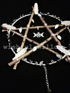 This beautiful pentacle has been made using willow sticks, silver plated and galvanised wire, silver tone leaf charms, a silver tone triple moon goddess charm with a pentacle centre, a strong steel ring, hematite beads, a hanging clear quartz drop with a silver tone cone and chain, clear quartz points and snowflake obsidian chips. Should you want the central charm changed or any other parts of the design customised I would be happy to help. There is a black cotton cord at the top of this…