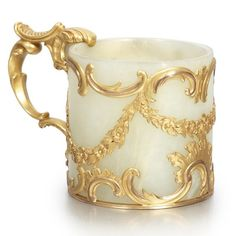 FROM THE ESTATE OF FRANCES H. JONES: A Fabergé Gold-Mounted Bowenite Small Cup, Workmaster Michael Perchin, St. Petersburg, circa 1890, in the Rococo taste, the carved cylindrical bowenite cup mounted à cage with a series of floral swags hanging from finely chased scrolls, the handle similarly made of up a number of shell scrolls and a ridged thumbpiece. Purchased by Tsar Alexander III on July 31, 1893.: