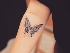 tatouage main homme, tenue pantalon et t-shirt noir, tatouage sur le bras en design papillon