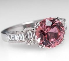 Pink tourmaline ring with a 3.2 carat round brilliant cut center stone. Shoulders bezel set with an emerald cut diamond and channel set baguette cut diamonds. Sides are micropavé set with round brilliant diamonds and the ring is finished off with milgrain edging.