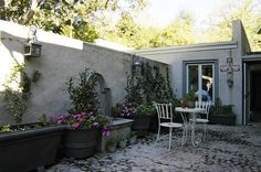 Beautiful French Country Cottage-style outdoor bistro patio or courtyard: stone or cement patio with planters, parlor table and chairs, lanterns, built-in fountain