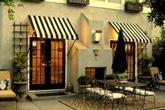 driftwood interiors: Stripe me lucky | Exterior with striped awnings opening out to a quaint patio bistro area.