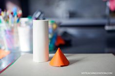 Toilet paper roll wrapped with white paper and orange paper cone