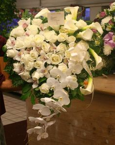 Funeral Heart flowers featuring orchids, roses and calla lilies.