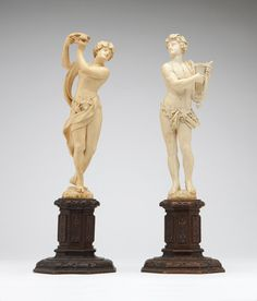 Continental carved ivory statues,  19th century, each depicting a classical figure of a musician, one plucking a lyre, the other tapping a tambourine, each on an integral base, mounted to an octagonal carved wooden plinth.