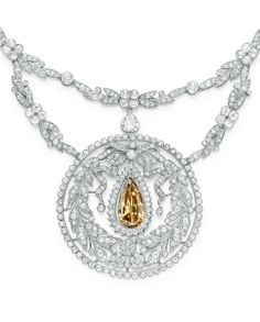 A BELLE ÉPOQUE COLOURED DIAMOND NECKLACE. Suspending a pear-shaped yellowish…