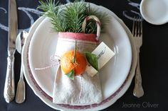 Christmas table place setting with flour sack bag, evergreen branches, candy cane, bakers twine, name tag, orange by Jeanne Oliver