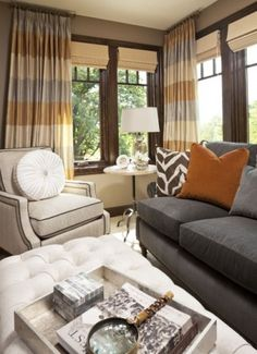 The dark-brown wooden window trim and shade coverings go perfect with those curtains. All furnishings in this image are available through Martha O'Hara Interiors, including the ottoman.
