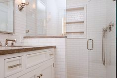 This master suite is all about convenience and luxury with a walk-in shower that has shelves built right into the wall. White tile covers the shower and wall space, while the counter tops are fixed with a complimenting marble stone.
