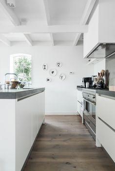 Strakke witte keuken met aanrechtblad van beton. Leuke styling met bordjes aan de muur!