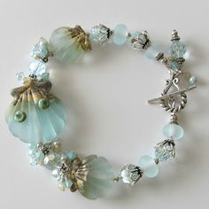 A gorgeous new lampwork seashell bracelet in pale aqua and sand tones.  The lampwork beads are complimented with Swarovski crystals and glass pearls.    http://itsbetterhandmade.com/misty-shores-lampwork-bracelet/