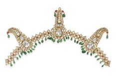 "AN IMPORTANT DIAMOND AND EMERALD TURBAN ORNAMENT (SARPECH)  Designed as three openwork ""jighas"" of graduated scrolled form, each set with a large central table-cut diamond within foiled gold surrounds, to the floral table-cut diamond border with ruby detail and emerald bead terminals, linked by twenty leaf-shaped diamond and ruby-set flexible panels suspending an emerald bead fringe, mounted in gold, Mughal or Deccani, late 19th century, 17 ins., (with two additional emerald beads)"