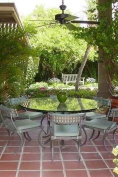 This garden patio has a round glass table and six chairs under a ceiling fan is surrounded by green potted plants and colorful flowers. It features vintage looking red tiles. #GardenPatioIdeas #OutdoorLiving #OUtdoorLivinigSpace  Courtesy of TopTenRealEstateDeals.com Ceiling Beams, Ceiling Fan, Room Design Software, Glazed Walls, Red Tiles, Home Room Design, All In The Family, Brick Flooring, Cozy Nook