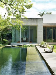 For an art-loving family in São Paulo, architect Isay Weinfeld devised a home comprising six interconnected blocklike structures. The swimming pool features a chemical-free filtration system, utilizing a separate regeneration area filled with aquatic plants and fish for water purification; the poolside lounges are Willy Guhl cement Loop chairs.