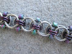 This beaded chainmaille bracelet is made with stainless steel jump rings, enameled copper jump rings in a dark purple color, and iridescent purple and green glass seed beads. It is 1/2 an inch (1.3 cm) wide, and has a gunmetal toggle clasp for the closure. I have a large variety of beads and jump rings if you would like this bracelet in a different colors. Just send me a message and I will make a custom bracelet for you.  Note: This bracelet should be kept out of water to preserve the color…
