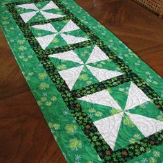 This lovely tablerunner top was pieced using a green shamrock print. The narrow inside border is a black print cotton. The machine sewn binding is the same as the outer border. I machine quilted it using Quilters Dream poly batting. Size: 15 1/2 x 42 Machine Wash Cool Tumble Dry Low