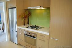 #Kitchen Idea of the Day: Modern Light Wood Kitchen with a light green glass pane backsplash.