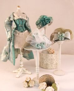 This miniature aqua silk dressing robe and corset to match are finished in contrasting silk bows and silk lace. Hats in silk with chiffon ribbon and silk bows and roses with beautiful feathers curled to tease the brim.