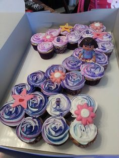 Put cupcakes frosted in Dora colors in the shape of a four with one cupcake having a Dora toy on it?