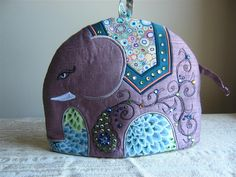 Gayle is a gorgeous embroidered elephant tea cosy who will keep your tea hot in style! The fabrics are a silk dupioni base with a teal silk and multi print blanket and green/blue floral background. They have been appliquéd, embroidered and accented with Swarovski crystals. Fleece interlining and a polar fleece lining make this cosy practical as well as beautiful. There is a loop for hanging so you have can art that is useful right where you need it, when you need it. Both sides have been...