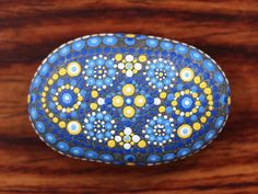 Moroccan Tile Mandala Stone Size: 3.5 x 2.25 Hand painted with acrylic paints and sealed with a matte varnish. Each stone is signed on the back by artist Rachel Keough. Ships beautifully packaged and ready for gifting. Care of your stone: • Please keep your stone indoors. •
