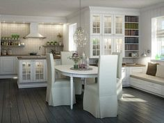such a pretty all white kitchen love the finish on the flooring and the window seat area