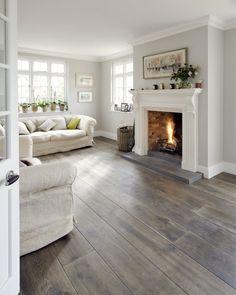 Idea camino classico con la cornice in marmo. Soggiorno contemporaneo moderno con le pareti grigio chiaro, divani color crema e pavimenti in legno massello