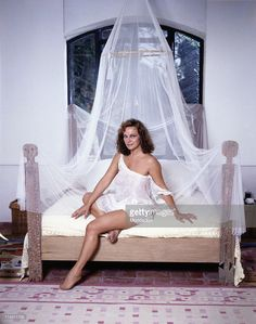 Portrait of Italian actress Laura Antonelli sitting on a four-poster bed wearing a baby doll. Italy, 1989.
