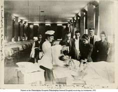 A doctor, a nurse, and other healthcare professionals surround a patient receiving eye treatment at the Philadelphia General Hospital, 1902. From the University of Pennsylvania School of Nursing.