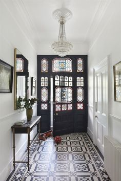 This modern hallway is flooded with light thanks to the stained glass in the door, which perfectly compliments the tiled floor in this stunning urban home. The modern hallway design is complemented with framed pictures and a statement light feature. London Townhouse, Victorian Townhouse, Victorian House Interiors, Townhouse Interior, Victorian Terrace House, Modern Townhouse, Interior Design Victorian House, Home Interiors, Brownstone Interiors
