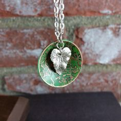 "Staring with a 1.25 inch copper disk, I hand draw a design that is then etched.  Adding a ""patina"" in greens and a simple leaf charm finishes this piece.Chain is 30"" silver plated sku:15808"