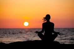 Meditation, woman silhouette, sunset, near the sea, free your mind, relax.
