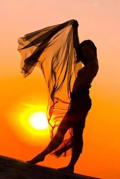 Woman praising the Lord in dance with scarf at setting golden sun. Gorgeous Prophetic art painting idea.