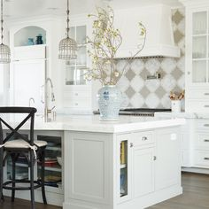 elegant kitchen with white cabinets, contrasting island, focal point backsplash