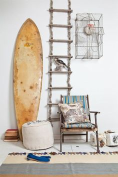 Coastal details including weathered looking wood furniture and an old surfboard
