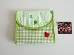 - Confeccionado em tecido 100% algodão <br>- 01 bolso interno com zíper <br>- 02 divisórias, sendo uma para band-aid <br>- fecho botão de pressão <br>- pingente no zíper <br> <br>Dimensões fechado: 13 x 12cm