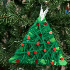 Use basic craft supplies to create this easy yarn wrapped Christmas tree ornament. It's a great craft for adults and kids to make together.