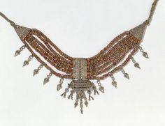 This necklace, called a lazem, has a pendent amulet case in its centre. The silver beads between the pieces of coral are typical of Yemeni jewellery. They are made of granules soldered together in pyramids, called tut, because they resemble mulberry berries. The lengths of braided cotton at the ends of the necklace are also typical. The original owner saw no need to extend the expensive silver and coral work behind her head, where it could not be seen. Yemen, circa 1850-1900