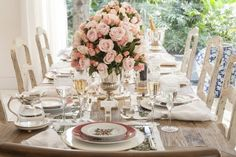 mesa de jantar clássica para uma recepção sofisticada. Centro de mesa com flores rosa claro, louça branca com estampa de flores e peças de prata.