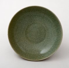 Longquan stoneware bowl. The bowl has a fine, pale grey body and closely crackled greyish-green glaze. There are overlapping lotus petals carved on the exterior. Where exposed, the body is reddish. The foot rim is unglazed. Yuan dynasty 13th/14th Century. The British Museum.  © The Trustees of the British Museum