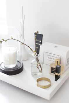 A tray with a scented candle, perfume, hand lotion and some flowers is all it takes to add a little luxury feeling in the bedroom.