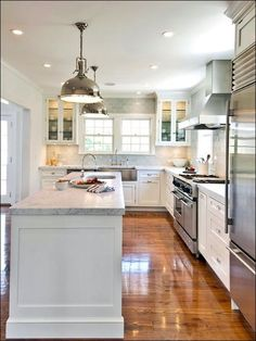 Beautiful L-Shaped Kitchen with Island and White Cabinets Paired with Marble Countertops