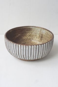 A bowl the perfect size for a one-dish meal. Hand-carved with a line pattern, and glazed milky white outside. Inside is a a storm of rust and creamy tones.Frien