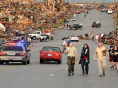 Residents of Joplin, Mo, walk west on 26th Street near Maiden Lane after a tornado hit the the southwest Missouri city, May 22, 2011.