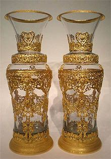 """A rare and stunning pair of """"Palace"""" Baccarat crystal vases from the Empire Period. Both covered with gilded bronze cagework (ormolu), depicting figures and faces.   Height: 30"""" inches."""