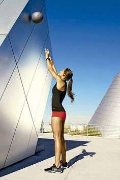 Balón de pared: párate con las piernas abiertas al ancho de las caderas, sosteniendo el balón a la altura del mentón con los codos hacia fuera. Haz una sentadilla hasta que los muslos queden paralelos al piso. Salta y extiende los brazos al tiempo que avientas el balón contra la pared (como en la foto). Agárralo e inmediatamente regresa a la posición inicial. Hazlo 45 segundos y descansa 15.  Trabajas: hombros, pecho, brazos, espalda, abdomen, glúteos, muslos.