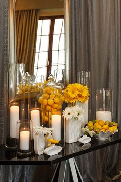 The juxtaposition of pillar candles in tall hurricanes, bright gerbera daisies, lemons and orchids make for fabulous decor.