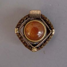 "VICTORIAN hair pin with orange cabochons center stone, hair frame set in gold, monogrammed ""MBF"", 1""."