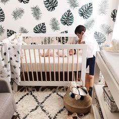 Gorgeous nursery with palm leaf print wallpaper and Moroccan shag rug